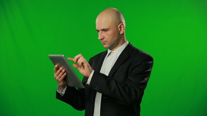 Bald businessman with tablet at green background.FULL HD