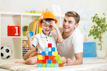 child and his dad play with building blocks