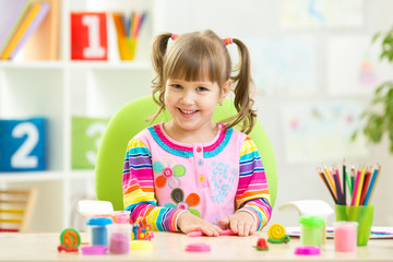 child girl playing with colorful clay