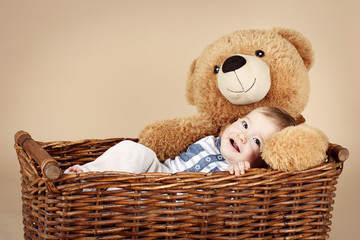 Little baby boy lying in the wicker basket with plush teddy bear