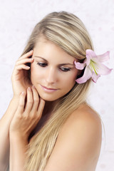 Beautiful face of young blond woman wearing lily
