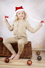 Beautiful child wearing christmas cap sitting on wicker