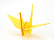 Traditional Japanese origami crane made of yellow paper over whi