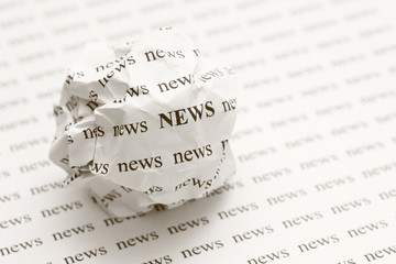 Crumpled paper ball with words news