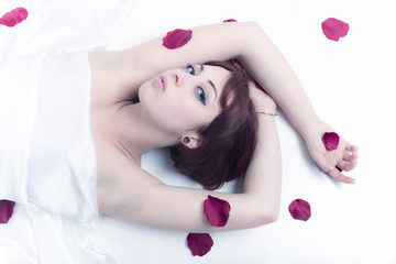 Woman portrait with petals of roses