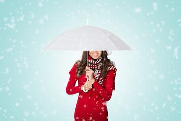 Snow falling on woman under umbrella