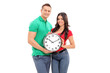 Young couple holding a big wall clock