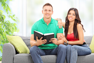 Young couple reading a book at home