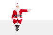 Santa sitting on a panel and pointing with finger