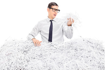 Worried man covered in shredded paper