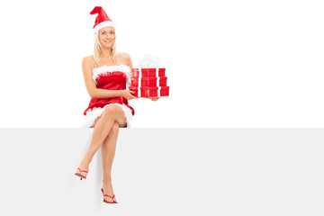 Girl in santa costume holding gifts seated on panel