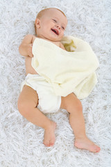 Cute baby boy with towel on carpet in room in room