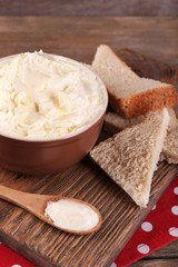 Fresh homemade butter in bowl and sliced bread,