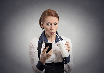 surprised woman reading news on smartphone drinking soda