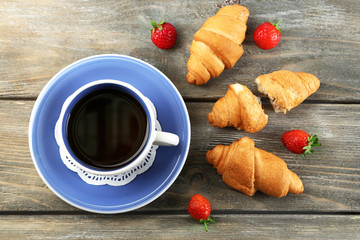 Breakfast with tea and fresh croissants on wooden background