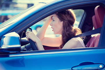 displeased stressed female car driver driving in heavy traffic