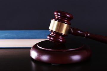 Judge's gavel and blue book on dark grey background