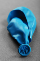 Popped blue balloon on paper background