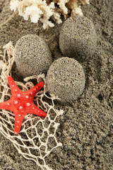 Sandcastles with starfish on sandy beach background