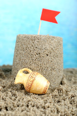 Sandcastle with flag on sandy beach