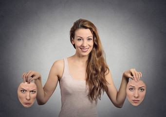 young smiling girl holds two face masks on grey wall background