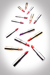 Different-colored lipsticks on white background