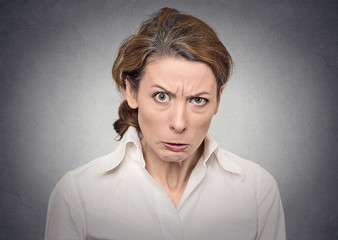 portrait headshot angry woman isolated on grey wall background