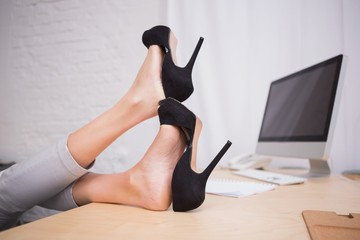 Businesswoman with high heels on desk