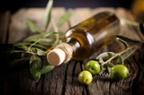 Olive oil and green olives on a wooden table