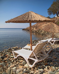Greek island, tranquil beach with umbrellas and chairs