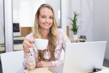 Cheerful businesswoman using her notebook holding a cup