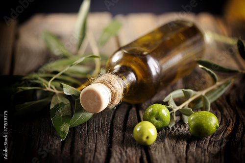 Fotobehang Kruiderij Olive oil and green olives on a wooden table