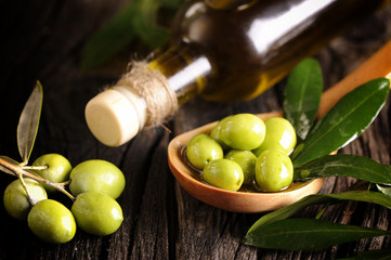 Olive oil and green olives on a wooden spoon