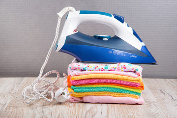 children's clothing and a steam iron on a light backgroundм