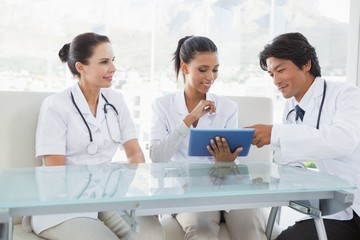 Smiling doctors using a tablet pc