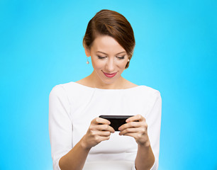 smiling woman texting on smartphone on blue background