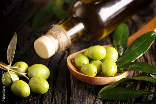 canvas print picture Olive oil and green olives on a wooden spoon