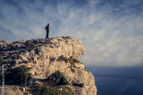 canvas print picture Man on a rock admiring the horizon