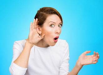 nosy woman with hand to ear gesture isolated on blue background