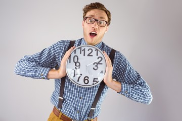 Geeky businessman holding a clock