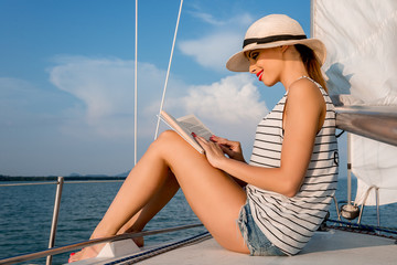 Young woman reading a book in a luxury boat.