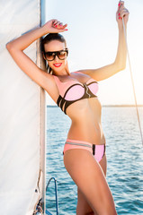 Yung sexy woman  posing on yacht in swimsuit.