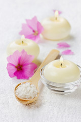 spa composition with sea salt, pink flowers and burning candles