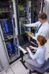 Team of technicians using digital cable analyser on servers