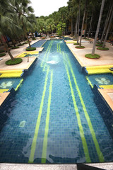 A big swimming pool with clear water and seats in water