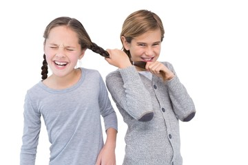 Angry young boy pulling sister hair in a fight