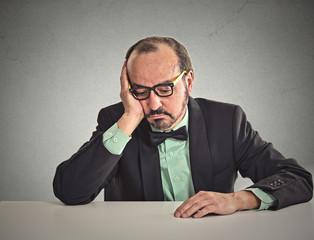 Desperate businessman sitting leaning on a desk looking down