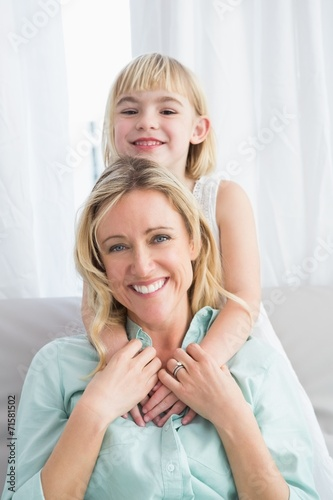 canvas print picture Portrait of a mother and daughter behind her on the couch