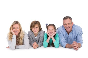 Cute family lying on the floor smiling at camera