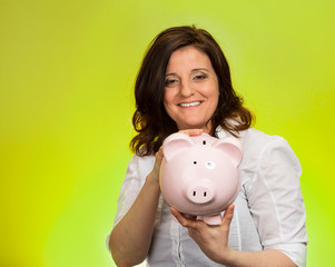 Happy woman holding piggy bank on green background